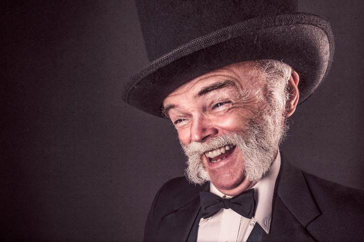 alter mann in klassischer garderobe mit Zylinder lacht