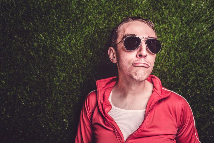 Hipster mit Sonnenbrille und Sportjacke auf Rasen