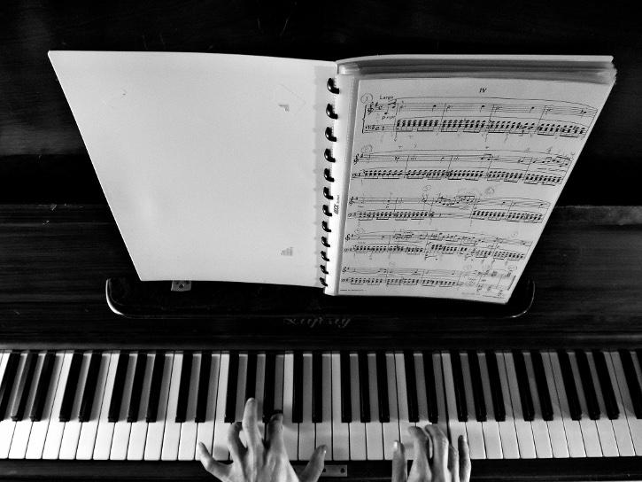 Klaviertastatur mit Noten und Pianist